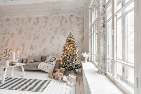 Light living room with Christmas tree. Comfortable sofa, high large Windows. Light white brick wall.