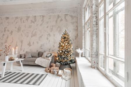 Soggiorno luminoso con albero di Natale. Comodo divano, grandi finestre alte. Muro di mattoni bianco chiaro. Archivio Fotografico