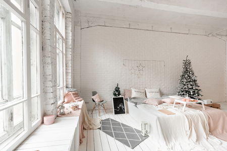 Christmas morning, Breakfast in bed, coffee and desserts. Loft style apartments. Bed in the bedroom, high large Windows. Brick wall with candles and Christmas tree. White color. Stock Photo