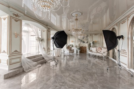 Photo Studio interior. classic luxurious apartments with a white fireplace, sofa, large windows and chandelier.