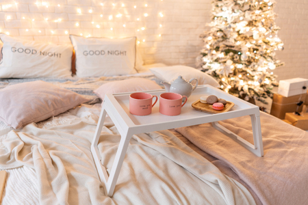 breakfast in bed, tray with cup of coffee and macaroon. Modern bedroom interior. Romantic morning surprise. Stockfoto