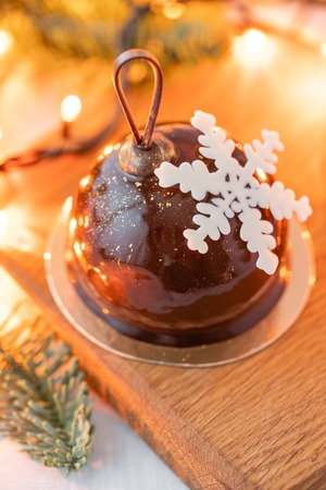 Mini mousse pastry dessert with chocolate glazed. Garland lamps bokeh on background. Modern european cake. French cuisine. Christmas theme. Snowflake