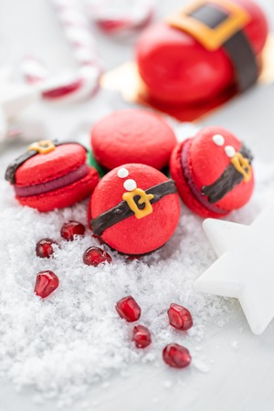 Funny cookie in the form red santa belly on gray table sprinkled with snow. Modern european French cuisine. Christmas theme, Merry Christmas card. New year mood. Variety of sweet macaroons.