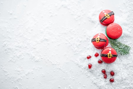 Funny cookie in the form red santa belly on gray table sprinkled with snow. Modern european French cuisine. Christmas theme, Merry Christmas card. New year mood. Variety of sweet macaroons. copy space