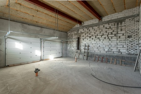 Large garage for two cars with of the gate. overhaul and reconstruction. Working process of warming inside part of roof. House or apartment is under construction, remodeling, renovation, restoration.