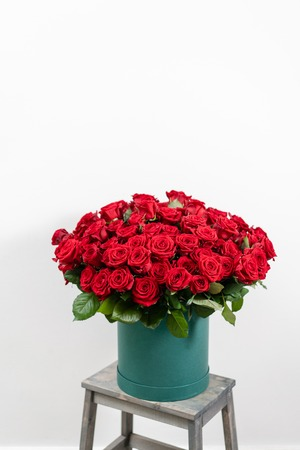 Big luxury bright bouquet on wooden table. One hundred of garden red roses. Color passionately scarlet, Autumn mood. bouquet in a hat box Banco de Imagens