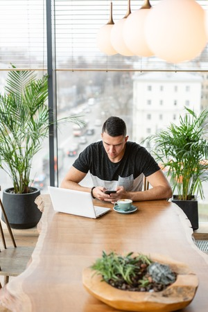 Freelancer work on netbook in modern coworking. Young man drinking coffee from a Cup. Programmer at remote job. Successful people, businessman in comfortable cafe. High large Windows