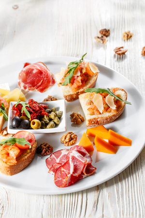 Plate with Italian appetizers. Bruschetta with a cherry tomatoes and shrimps. Parmesan cheese, prosciutto, green capers, olives, sun-dried tomatoes and walnuts.