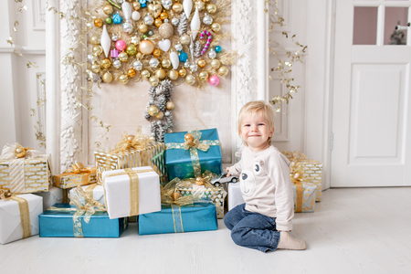 A little boy stands near a lot of gifts. Happy new year. decorated Christmas tree. Christmas morning in bright living room Stock Photo