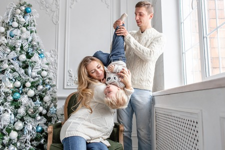 Young parents fool around and play with little son. Happy family having fun at home. Christmas morning in bright living room. Father, pregnant mother and their baby boy. Happy new year. Upside down Stock fotó
