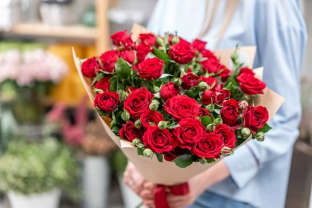 bouquet in the hands of a cute girl. garden red spray roses. Color passionately scarlet, Autumn mood Banco de Imagens