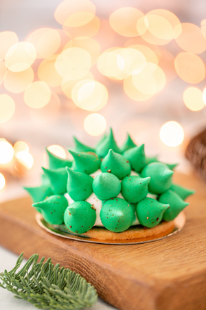 Mini mousse pastry dessert with green meringue. Garland lamps bokeh on background. Modern european cake. French cuisine. Christmas theme