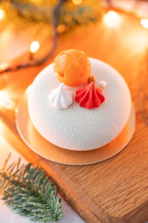 Mini mousse pastry dessert covered with white velour. Garland lamps bokeh on background. Modern european cake. French cuisine. Christmas theme Imagens