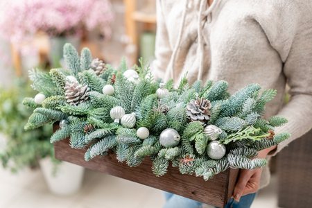Workshop of Christmas decor with their own hands. Christmas wooden box with fir branches for the holiday. The new year celebration. Stock Photo