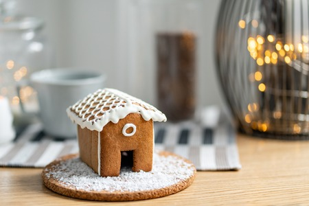 Gingerbread house on wooden table. Defocused garland lights on background. Christmas tree and Holiday mood. Morning in the bright living room.