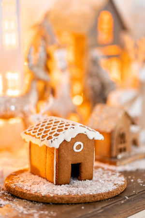 Christmas decorations and Holiday mood. Morning in the bright living room. Gingerbread house on wooden table. Defocused garland lights on background.