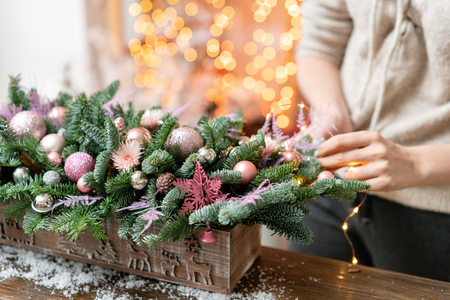 Young woman creates and decorates beautiful festive arrangement of fresh spruce, ornamentals in a rustic wooden box box. Christmas mood. Garland bokeh on background.