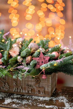 Beautiful festive arrangement of fresh spruce, pink ornamentals in a rustic wooden box box. Christmas mood. Garland bokeh on background. Banque d'images
