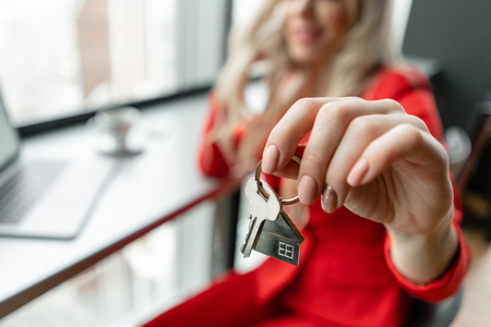 Mortgage concept. Woman in red coral business suit holding key with house shaped keychain. Modern light lobby interior. Real estate, hypothec, moving home or renting property. Banque d'images