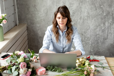 Young friendly smiling woman florist create ordering in the working base on a laptop. Flower delivery concept. Professional worker in a flower shop. Archivio Fotografico