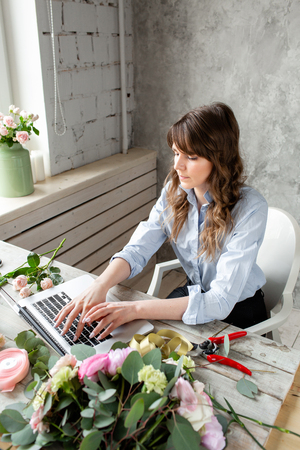 Woman blogger and content creators of social networks and blog flower shop. The concept of online store and floral delivery. SMM promotion. laptop keyboard and desktop of flower shop . Archivio Fotografico