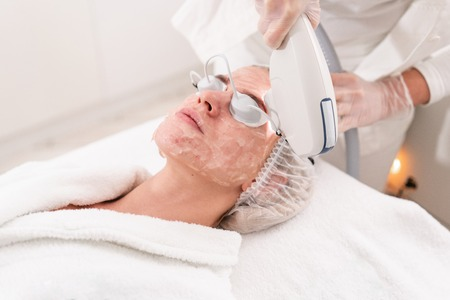 Anti acne phototherapy with professional equipment. Beautiful woman in beauty salon during photo rejuvenation procedure. Laser face skin treatment at cosmetic clinic. Hardware cosmetology Stock Photo - 114771471