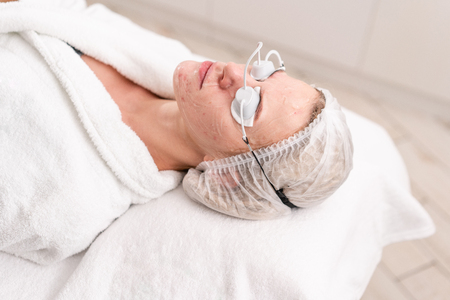 Portrait of a young woman patient. Anti acne phototherapy with professional equipment. Beautiful woman during photo rejuvenation procedure. Face skin treatment at cosmetic clinic. Stock Photo