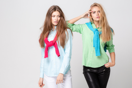 happy girlfriends women in shirts and a sweater on his shoulders. Fashion spring image of two sisters. Colorful colors clothes. Models with Blonde and light brown hair. Looking at camera and smiling.
