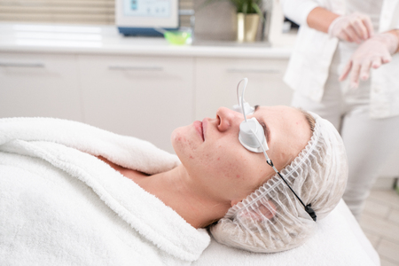The doctor puts the patient goggles. Anti acne phototherapy with professional equipment. Beautiful woman in beauty salon during photo rejuvenation procedure. Face skin treatment at cosmetic clinic. Stock Photo - 114771546