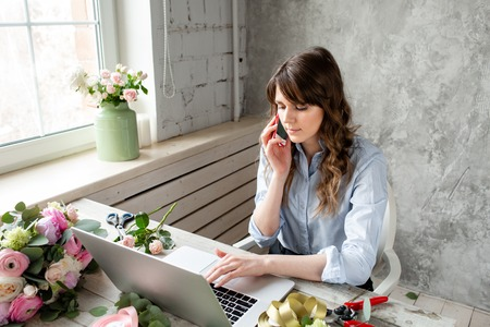 Young friendly smiling female florist talking on a mobile phone and create ordering in the working base on a laptop. Flower delivery concept. Professional worker in a flower shop.