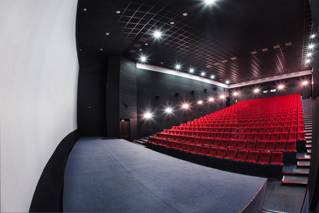 Russia, Nizhny Novgorod - may 23, 2014: Mir Cinema. Empty red cinema hall seats, comfortable and soft chairs. Perspective auditorium view with white space on the screen