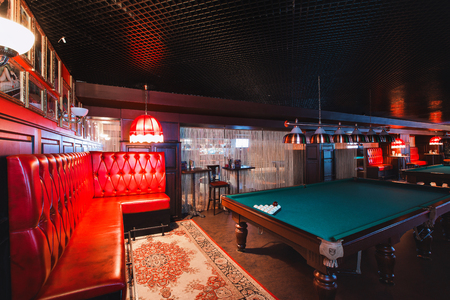 Russia, Nizhny Novgorod - may 26, 2014: Sormovsky Cinema and Entertainment center. Interior of a club having billiard tables illuminated with lights. large green pool table
