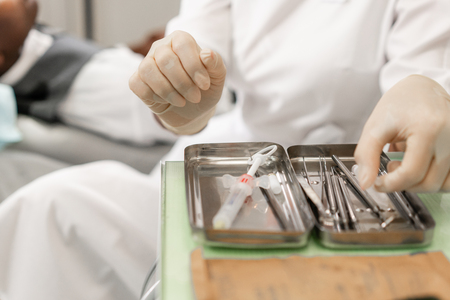 Dental instruments in the foreground. Woman dentist treating root canals in the dental clinic. Man patient lying on dentist chair with open mouth. Medicine, dentistry and health care concept.