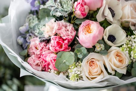 mooi vers gesneden boeket van gemengde bloemen in vaas op houten tafel. Het werk van de bloemist bij een bloemenwinkel. Delicate Pasteltinten kleur