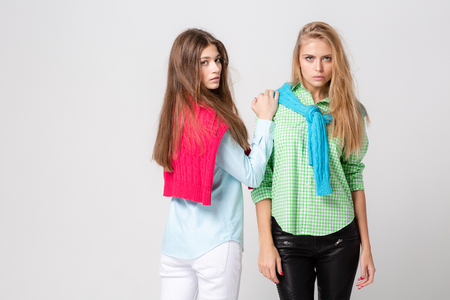 happy girlfriends women in shirts and a sweater on his shoulders. Fashion spring image of two sisters. Colorful colors clothes. Models with Blonde and light brown hair.