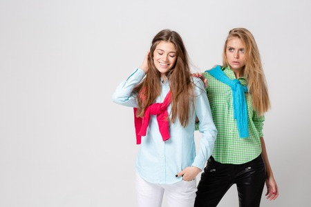 happy girlfriends women in shirts and a sweater on his shoulders. Fashion spring image of two sisters. Colorful colors clothes. Models with Blonde and light brown hair. Looking at camera .