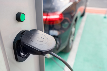 Close up of the power supply plugged into an electric car being charged. Electric car charging station. Concept of environmentally friendly engine