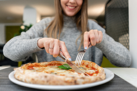 Woman eats with knife and fork a pizza Margherita with mozzarella tomatoes and basil. Neapolitan pizza from wood-burning stove. lunch in an Italian restaurant. Table near to a large window. 스톡 콘텐츠