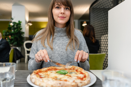 Woman eats with knife and fork a pizza Margherita with mozzarella tomatoes and basil. Neapolitan pizza from wood-burning stove. lunch in an Italian restaurant. Table near to a large window. Stock Photo