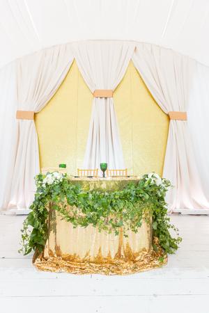 La tavola degli sposi. Piatti dorati, bicchieri da vino verdi e tovaglioli. Concetto di ristorazione. Interno della tenda per il pranzo di nozze, pronto per gli ospiti. Servito tavola rotonda banchetto.