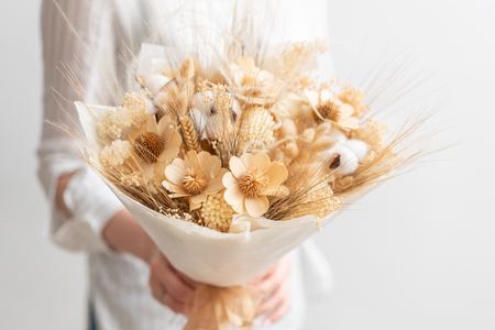 beautiful bouquet of mixed dried flowers in woman hand. the work of the florist at a flower shop. Delicate Pastel tones color