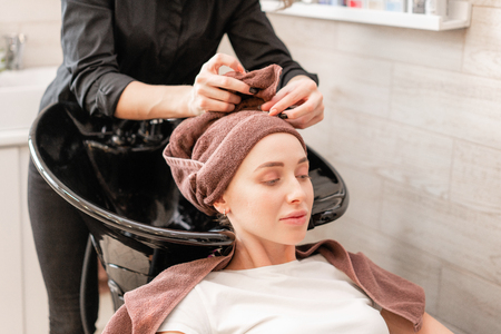 beautiful girl washes her hair before a haircut in a beauty salon. hair washing at a hairdressing. professional shampoo. stylist hairdresser
