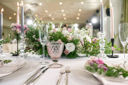 Closeup Table setting with plates and tableware, adorned with flowers. Floral decoration for wedding ceremony romance dining. Wedding banquet , festive decor. Concept of service and catering. Stock Photo