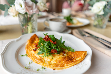Breakfast. Frittata - italian omelet. Omelette with tomatoes, arugula and soft cheese. Coffee and other dishes on the table in the restaurant