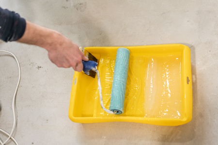 Paintbrush, roller and glue container on concrete surface. Composition tools for home repair and interior renovation indoors.