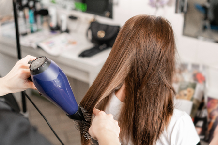 Young woman and hairdresser with fan making hot styling at hair salon