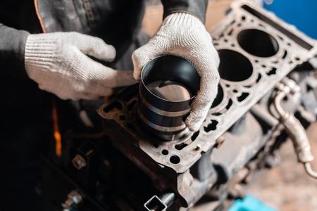 Nahaufnahme Automechaniker hält einen neuen Kolben für den Motor, Überholung.. Motor auf einem Reparaturständer mit Kolben und Pleuel der Automobiltechnik. Innenraum einer Autowerkstatt.