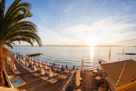 Tables in cafe. Summer sunrise on coast, Corfu island, Greece. Beach with Sunbeds and umbrellas with perfect views of the mainland Greece mountains. Stock Photo