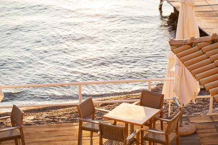 Tables in cafe. Summer sunrise on coast, Corfu island, Greece. Beach with Sunbeds and umbrellas with perfect views of the mainland Greece mountains.