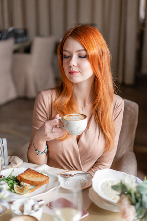 Nice redhead woman eat breakfast in cafe. Portrait of young charming female drinking coffee and toasted sandwich in modern coffee shop.